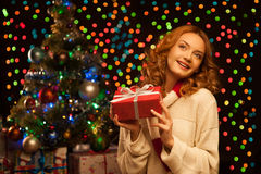 Young smiling woman holding red christmas gift Royalty Free Stock Image