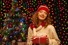 Young smiling woman holding red christmas gift. Young happy smiling casual woman holding red gift over christmas tree and lights on background. shallow depth of Royalty Free Stock Image