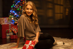 Young smiling woman holding red christmas gift Stock Photography