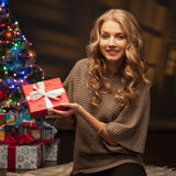 Young smiling woman holding red christmas gift Royalty Free Stock Photography