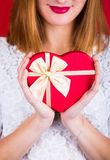 Young smiling woman holding red gift box in shape of heart on re Stock Photo