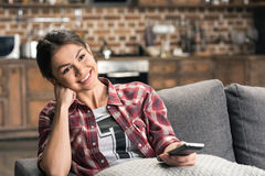 Young smiling woman holding remote control Royalty Free Stock Photos