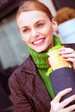Young smiling woman holding a sandwich Stock Images