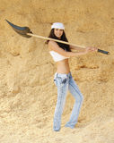 Young smiling woman holding spade. Portrait of young smiling beautiful brunette woman holding spade, standing in sawdust Royalty Free Stock Images