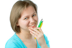Young smiling woman holding a two pens. Stock Photo