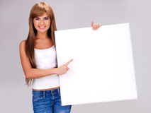 Young smiling woman holds white big banner Royalty Free Stock Image