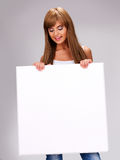 Young smiling woman holds white big banner Stock Photos