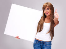 Young smiling woman holds white big banner Royalty Free Stock Photo