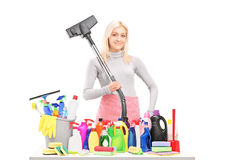 Young smiling woman with a hover and cleaning supplies on a table Stock Image