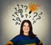 Questions and ides. Young smiling woman interrogation marks, light bulb and arrow mess above head. Question and idea concept. Find solution to problems royalty free stock image