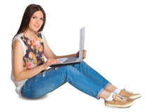 Young smiling woman in jeans with laptop sitting on floor. Isolated on white royalty free stock photos