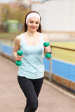 Young smiling woman jogging with dumbbells Royalty Free Stock Photo