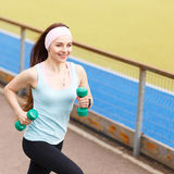 Young smiling woman jogging with dumbbells Stock Image