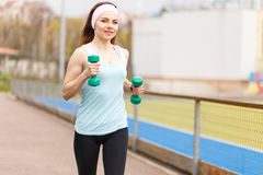 Young smiling woman jogging with dumbbells Stock Photos