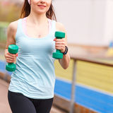 Young smiling woman jogging with dumbbells Royalty Free Stock Photography