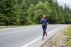 Young smiling woman jogging on mountain road. stock photo