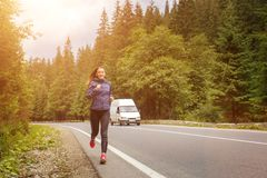 Young smiling woman jogging on mountain road. royalty free stock photography