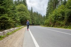 Young smiling woman jogging on mountain road. stock images