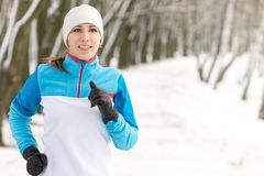 Young smiling woman jogging at winter morning in park Royalty Free Stock Images