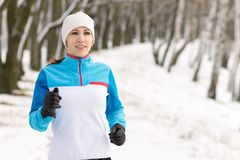 Young smiling woman jogging in winter park. Royalty Free Stock Images