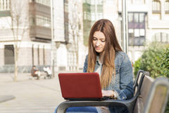 Young smiling woman laptop computer in the street. Stock Photography