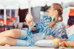 Woman enjoying coconut water. Young smiling woman leaning on pillow enjoying coconut water stock photography