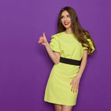Young Smiling Woman In Lime Green Dress Gives Thumb Up Royalty Free Stock Images