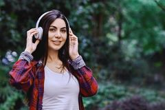 Young smiling woman listening to the music, through headphones on her head. Young smiling woman with bluetooth headphones on her head listening to the music royalty free stock images