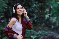 Young smiling woman listening to the music, through headphones on her head. Young smiling woman with bluetooth headphones on her head listening to the music stock images
