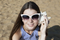 Young smiling woman listens to a seashell. On the beach sand. Closeup portrait. Beauty in nature Royalty Free Stock Photography