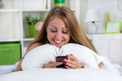 Young Smiling Woman Looking At Her Phone On The Bed Stock Photography