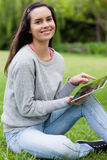 Young smiling woman looking at the camera while holding her tabl Royalty Free Stock Images