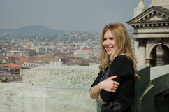 Young smiling woman looking at the cityscape Royalty Free Stock Photography