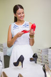 Young smiling woman looking at a shoe Royalty Free Stock Photo
