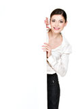 Young smiling woman looking from white blank banner Royalty Free Stock Photo