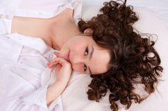 Young smiling woman lying on bed Royalty Free Stock Photos