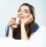 Young smiling woman lying in bed, hold water glass. Stock Photography