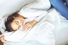 Young woman lying on bed hugging pillow Royalty Free Stock Images