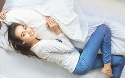 Young woman lying on bed hugging pillow Royalty Free Stock Photo