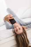 Young smiling woman lying in bed and taking self portraits with a smartphone Stock Images