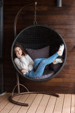 Young smiling woman lying in buble chair using smart phone Stock Photography