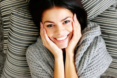 Young smiling woman lying on the floor with pillows. View from above Stock Photos