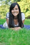 Young smiling woman lying in grass Royalty Free Stock Photography