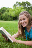 Young smiling woman lying on the grass in a park Stock Photo