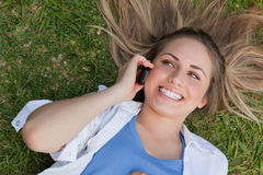 Young smiling woman lying on her back while using her cellphone. Young smiling woman lying on her back while calling while her mobile phone Stock Photography