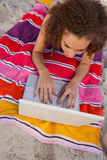 Young smiling woman lying on her beach towel while typing on her Stock Images