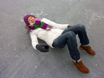Young smiling woman is lying on ice , frozen lake - winter outdoor scene