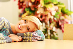 Young smiling woman lying on the table Royalty Free Stock Image