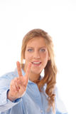 Young smiling woman making victory gesture Royalty Free Stock Images