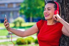 Young smiling woman making video call via smartphone and headphones. royalty free stock photo